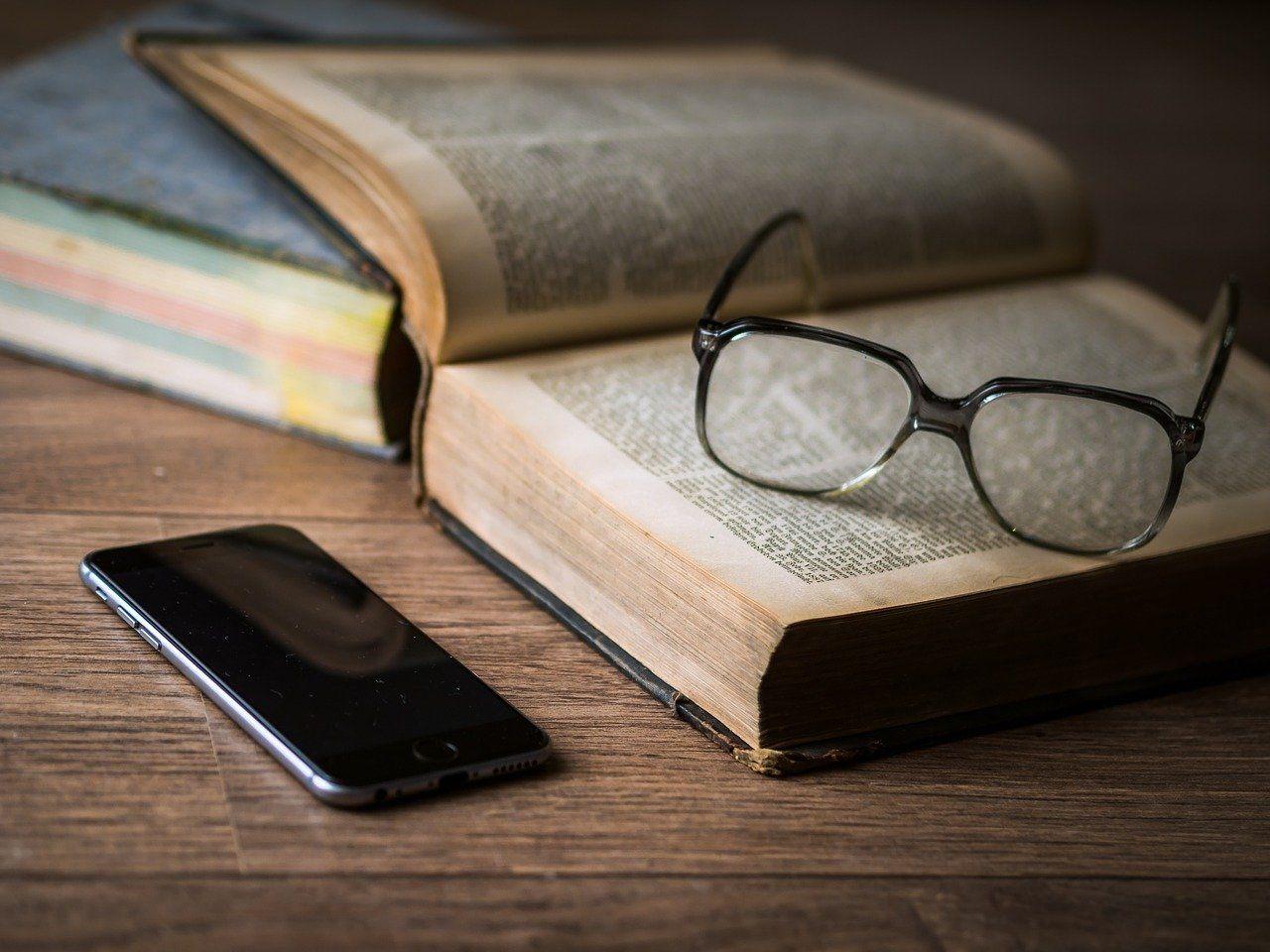 Livre ouvert avec lunette et smartphone